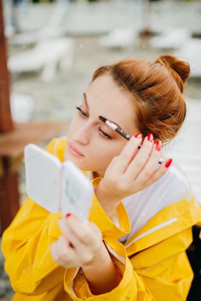 Woman doing makeup outside