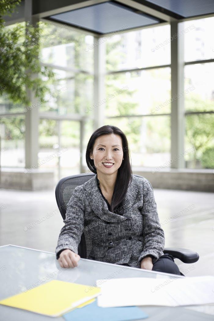Портрет азиатской бизнесвумен в холле конференц-центра.