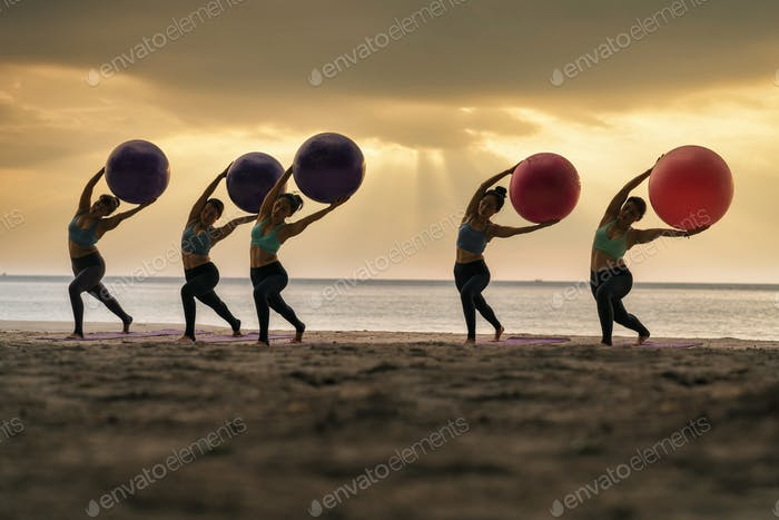 Group of club coaching for practicing yoga class with ball on the sea beach when sunset,