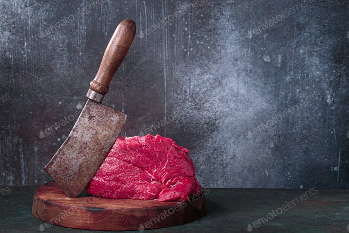 Raw beef and meat cleaver on chopping deck