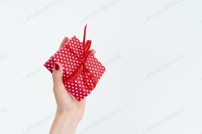 woman hand holding red gift with ribbon, manicured hand with nail polish