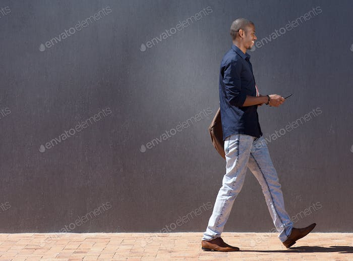 black male student walking with tablet
