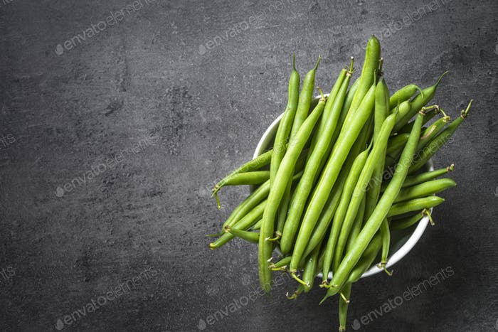 Green beans on black background