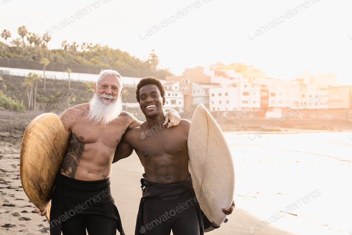 Multi generational surfer people having fun on the beach after sport surfing session