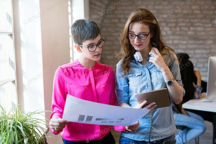 Gruppe junger perspektivischer Architekten mit Blick auf Projektpapiere