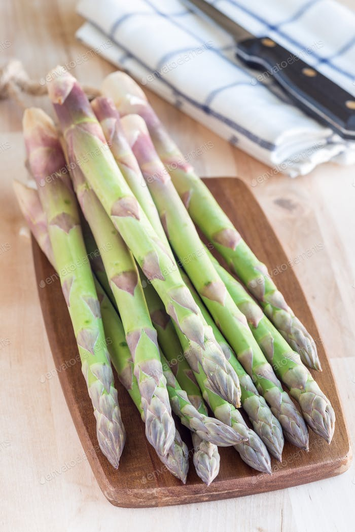 Bunch of fresh green asparagus on wooden board, vertical