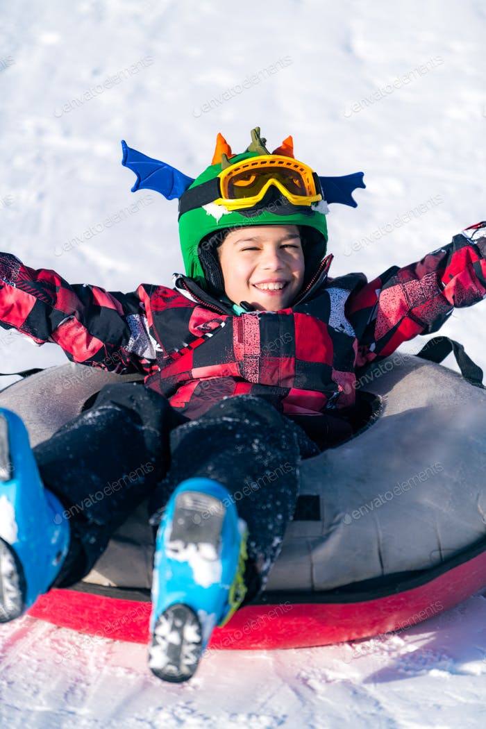 Boy Sledding in Snow Tube