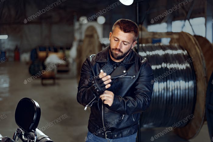 Biker man puts on his leather gloves for riding