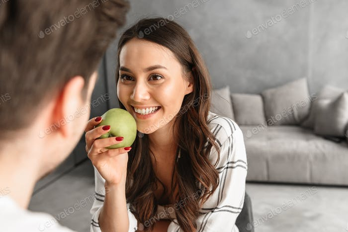 Image of attractive smiling woman looking at man, while sitting
