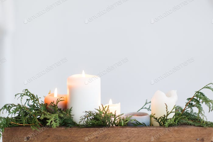 Burning candles in rustic wooden box with cedar branches on wooden table