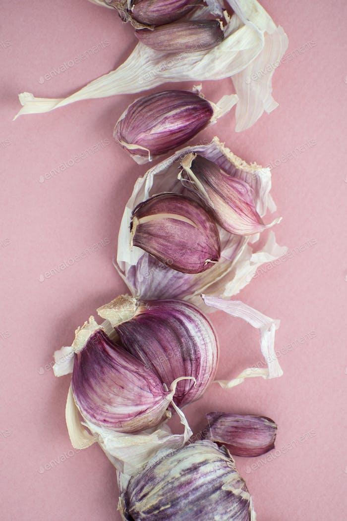 Knoblauchzehen und Schalen schließen sich auf einem weichen rosa Hintergrund.
