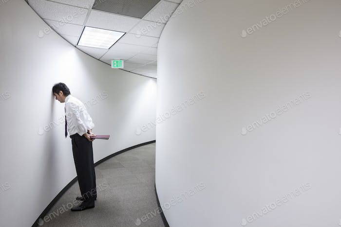 An asisan businessman frustrated and standing with his head against a wall in a hallway.