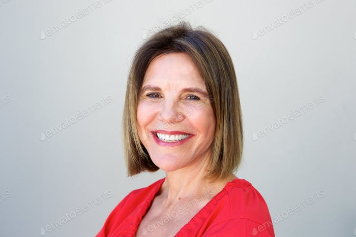 attractive older woman smiling by gray background