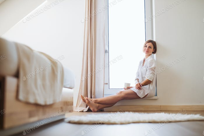 Thumbnail for A young woman with night shirt sitting by the window in the morning.
