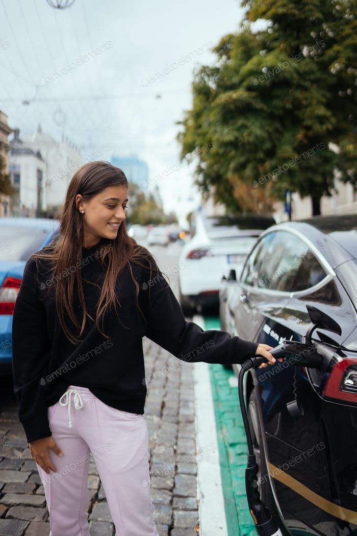 Woman near electric car. Vehicle charged at the charging station