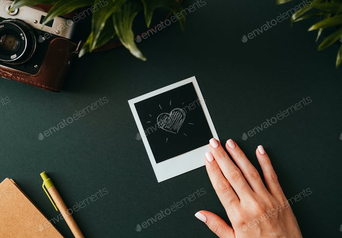 Female hand holds a polaroid picture with a heart