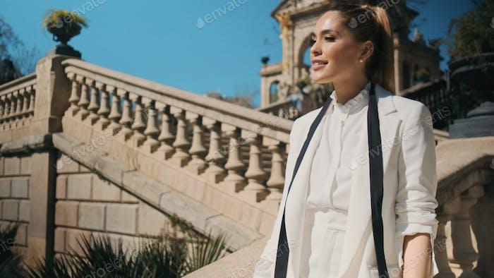 Porträt der schönen eleganten Frau im klassischen weißen Anzug zuversichtlich wegschauen in alten Park
