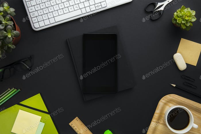 Digital Tablet Surrounded By Office Supplies On Gray Desk