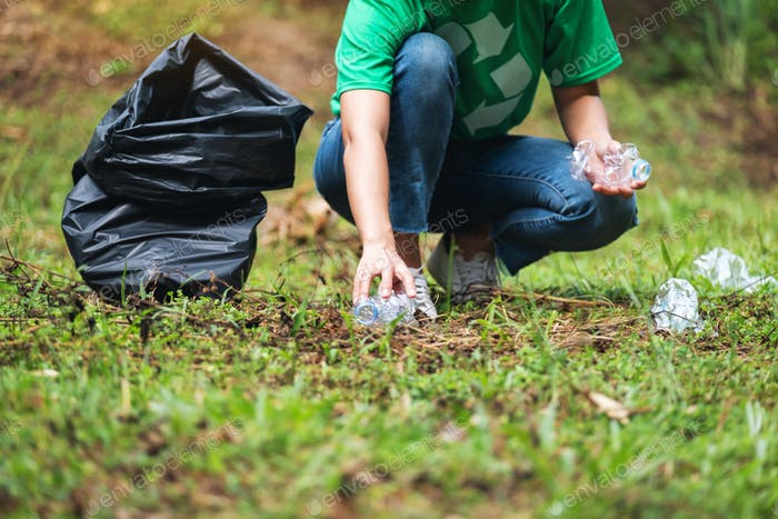 a female activist picking up garbage plastic bottles into a plastic bag in the park
