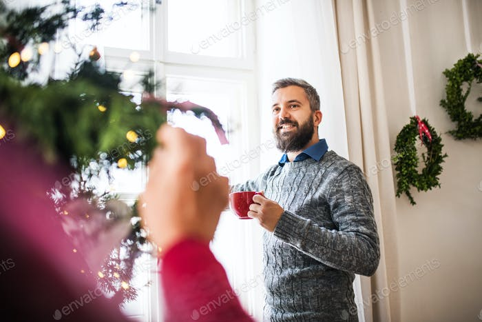 A hipster man talking to an unrecognizable person at home at Christmas time.