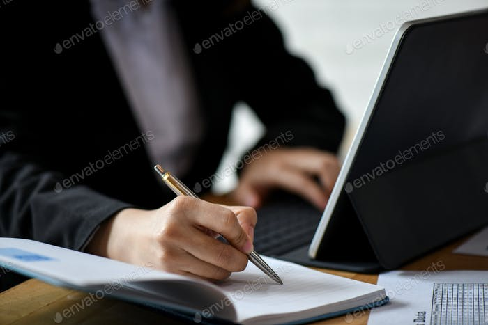 Office staff use laptop computer and note in notebook on desk.