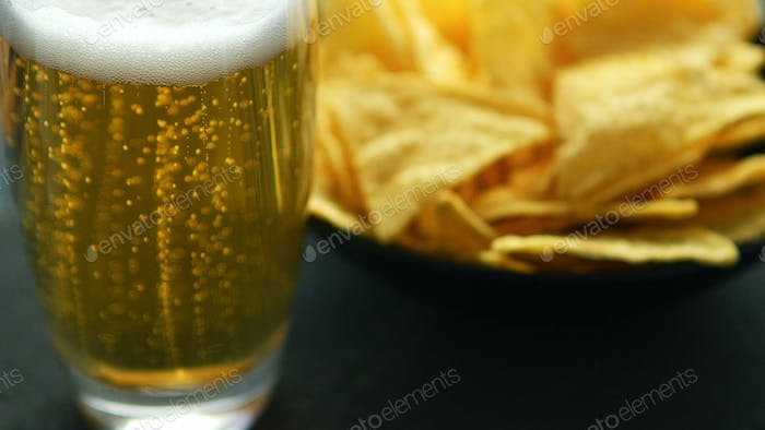 Glass of beer and nacho chips