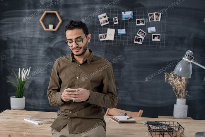 Young confident businessman in casualwear scrolling in smartphone in office