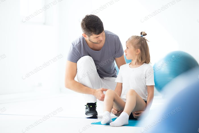 Cute school girl sitting on blue yoga mat talking to her handsome young physician