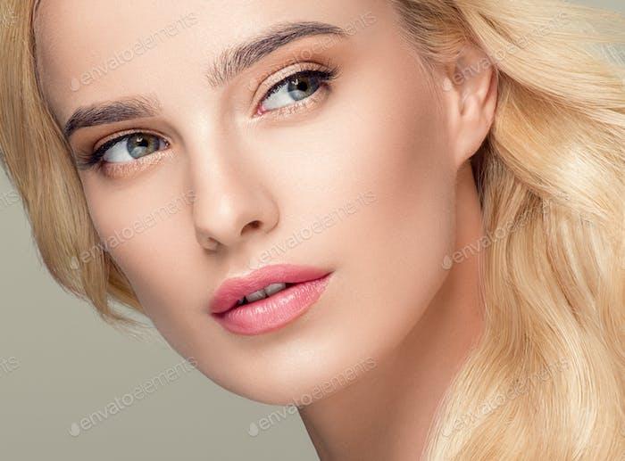 Blonde Hair Woman Beautiful Curly Hairstyle Wavy Long hair Natural Make up. Studio shot. On gray