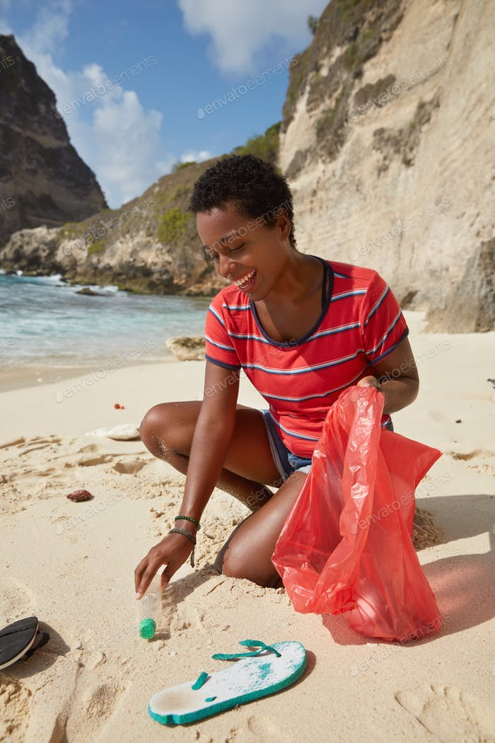 Volunteering concept. Responsible female tourist participates in beach cleaning event, collects plas