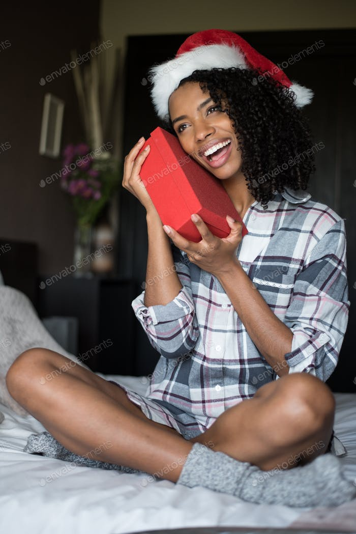 Beautiful cute black young woman in pyjamas on bed with Christmas hat and Christmas gift