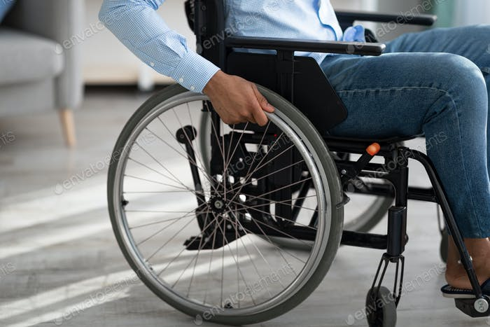 Cropped view of disabled black man sitting in wheelchair at home. Impairment and mobility aids