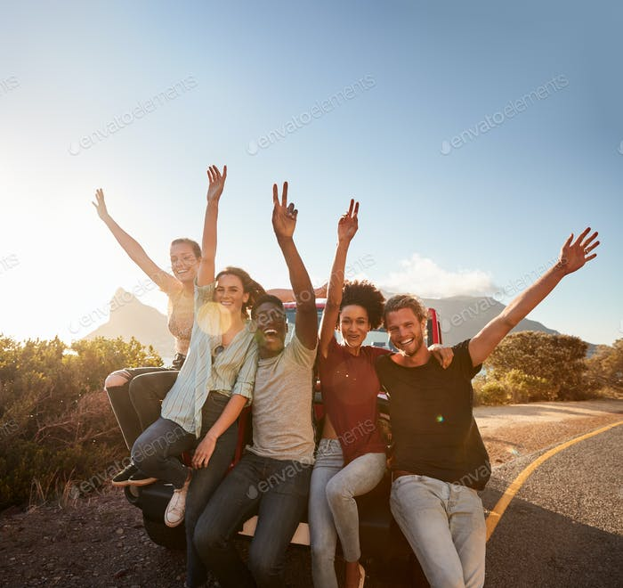 Five millennial friends on a road trip taking a break, leaning on the car waving to camera
