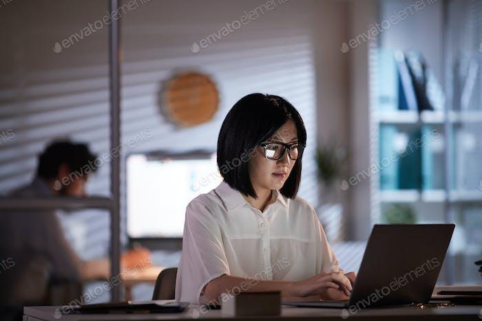Mujer asiática trabajando en el ordenador portátil