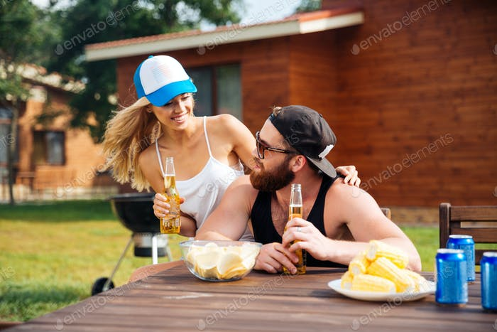 Happy young couple drinking beer outdoors together