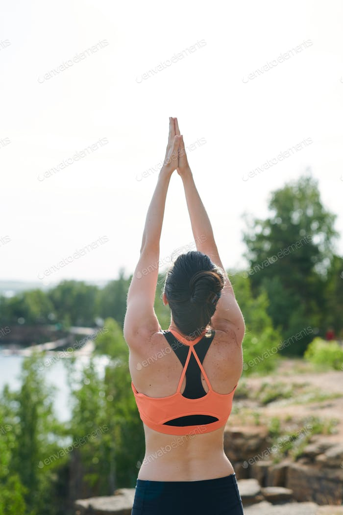 Rear view of young woman in sports bra standing on quarry and raising hands