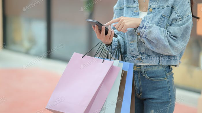 Young shopper is searching for information with a smartphone.
