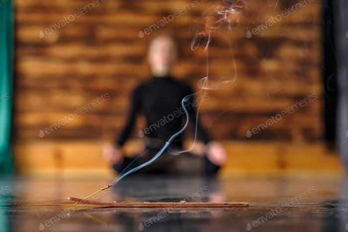 smelling burning stick and blurred woman at the back in lotus yoga pose
