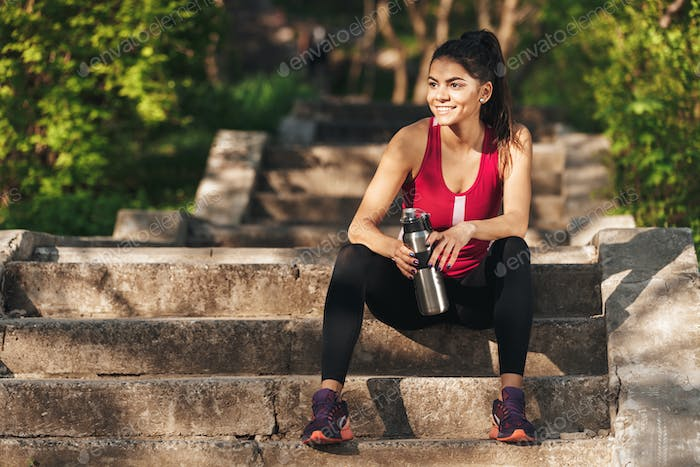 Smiling young sportswoman sitting on stairs with water bottle