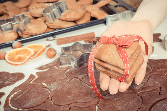 Hand of woman holding fresh gingerbread or cookies for Christmas time and accessories for baking