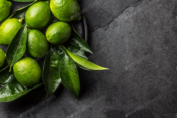 Green lemon Lime with fresh leaves on black plate, slate background