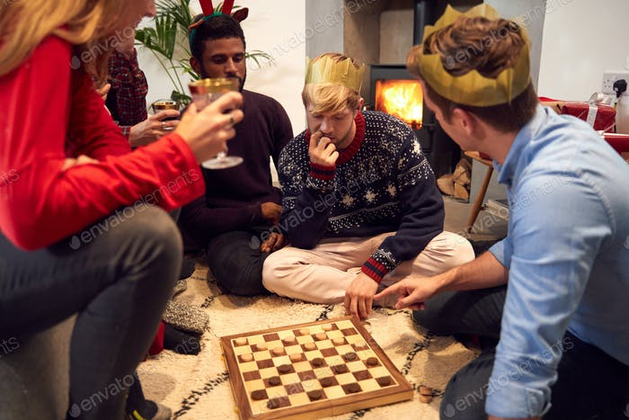 Group Of Friends Playing Board Games After Enjoying Christmas Dinner At Home