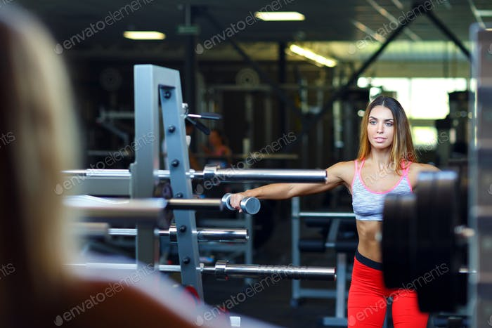 Beautiful woman with dumbbell in the gym doing exercises
