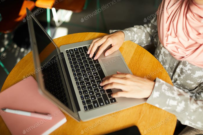 Hands of Muslim woman working on laptop