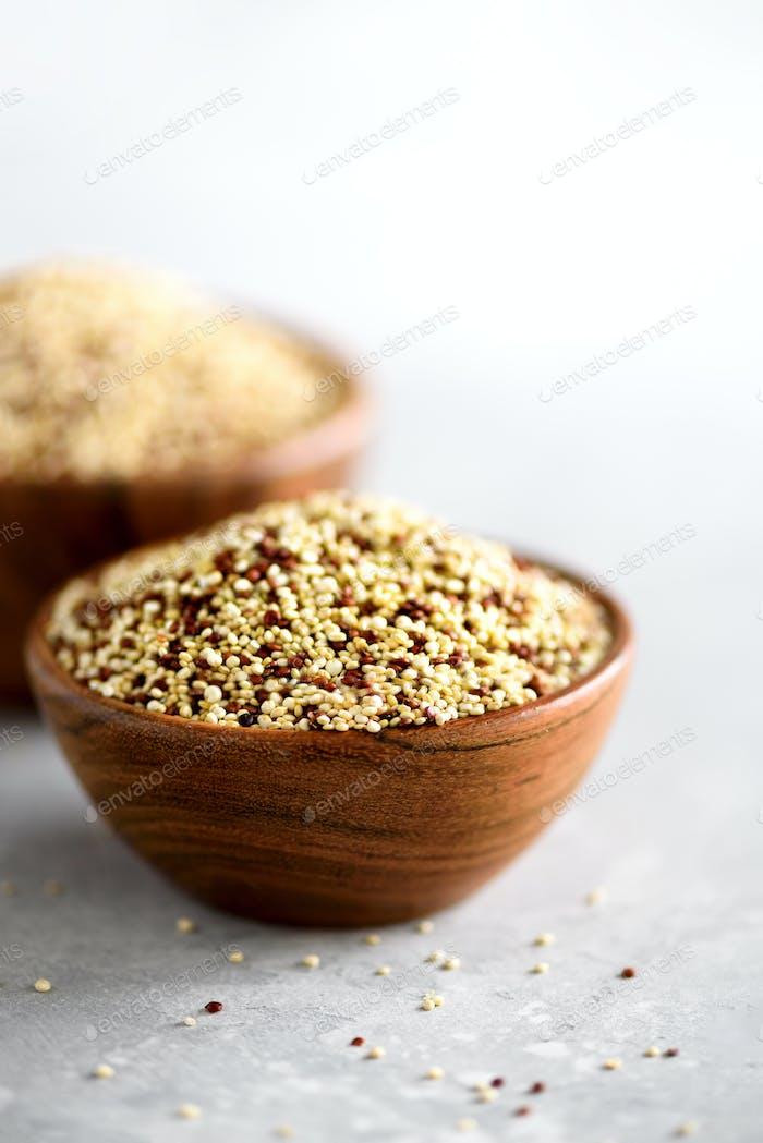 Weiße und rote rohe Bio-Quinoa in Holzschale und Rosmarin auf grauem Hintergrund. Gesunde Ernährung