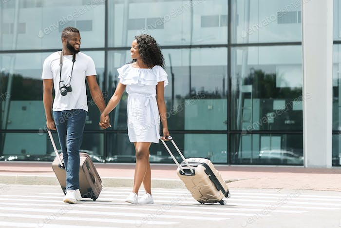 Happy black millennials going out of airport with luggage
