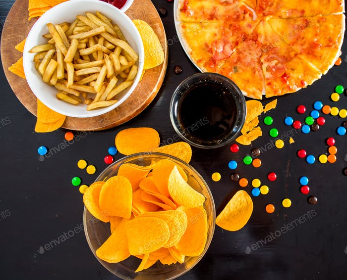 Fast food and unhealthy eating concept - close up of pizza,, french fries
