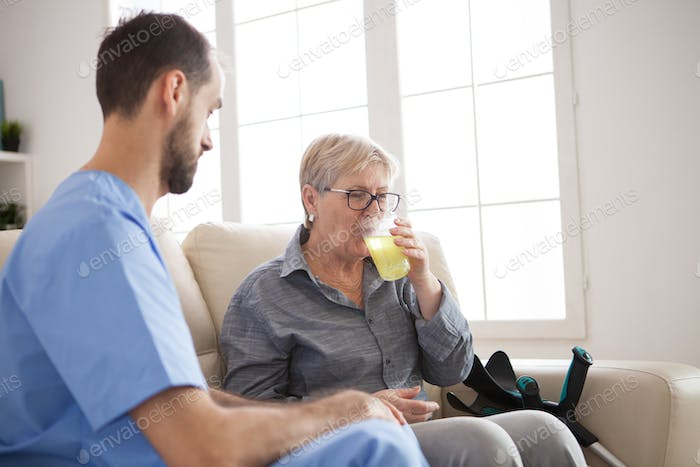Young caregiver sitting down on couch with senior woman