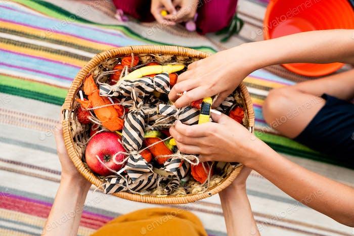 Overview of kid hands taking halloween treats from basket held by generous woman