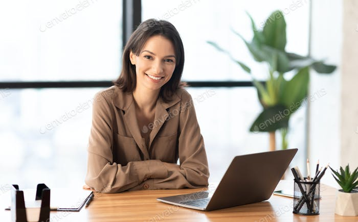 Young manager smiling at camera in office